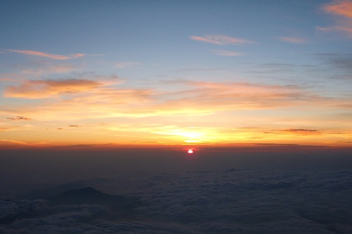 View of sunrise from Mount Fuji across clouds and smaller peaks