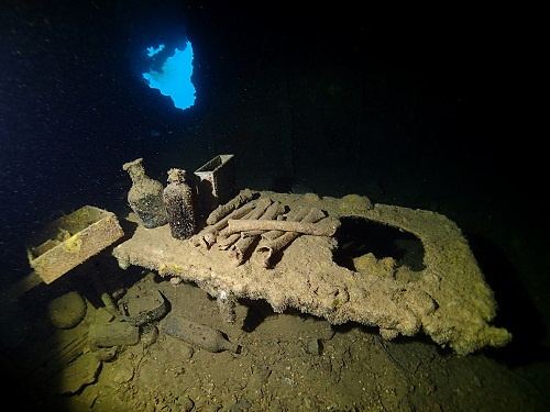 Surgeon's table topped with bottles and pile of bones on Shinkoku Maru in Chuuk Lagoon, Micronesia