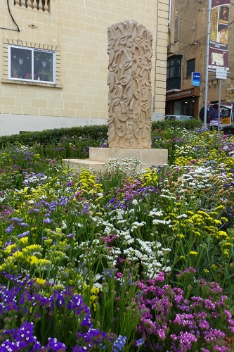 Flowers surrounding stone sculpture in Victoria, Gozo