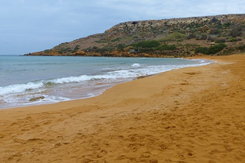 Orange sand and view to Calypso's Cave at Ir Ramla beach in Gozo