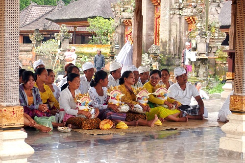 People sitting with offerings at ceremony at Ulun Danu Bratan temple in Bali, Indonesia