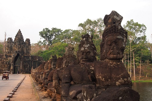 Statues seen cycling across bridge to South Gate of Angkor Thom in Siem Reap, Cambodia