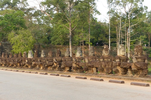 Row of statues seen cycling across bridge to South Gate of Angkor Thom in Siem Reap, Cambodia