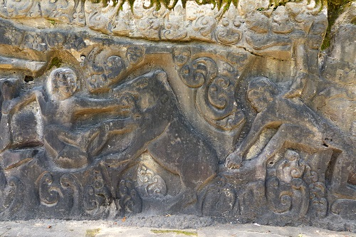 Rock carvings of a boar hunt at Yeh Pulu in Bali, Indonesia