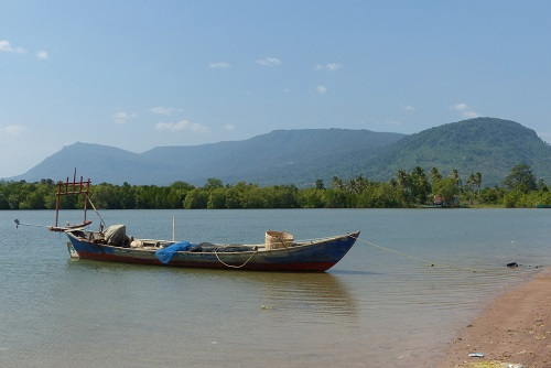 Boat moored by beach with view of Bokor Mountain in Cambodia