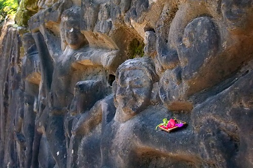 Flower offering on rock carvings at Yeh Pulu in Bali, Indonesia