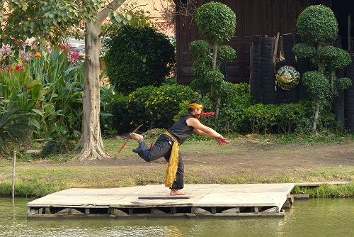 Man on one leg balancing swords at Ayutthaya Floating Market in Thailand