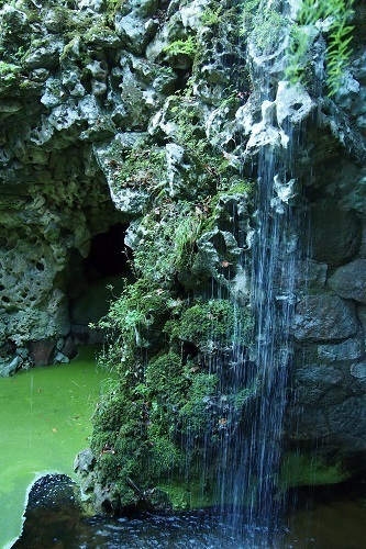 Waterfall and green pool at Quinta da Regaleira in Sintra, Portugal