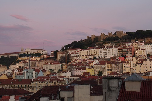 View of city and Sao Jorge Castle from rooftop bar in Lisbon, Portugal