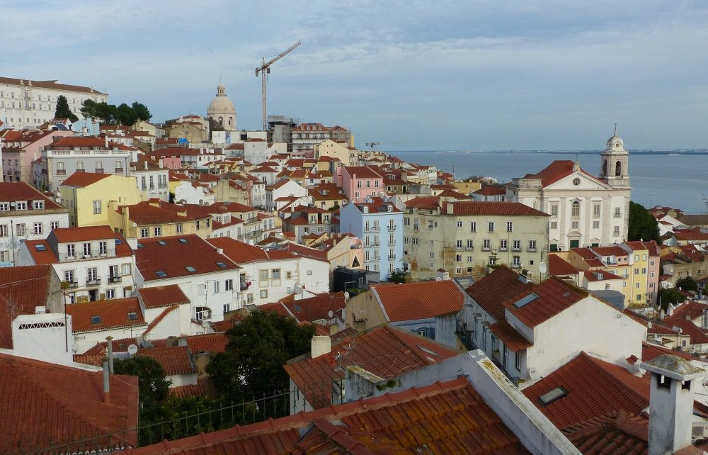 Church and houses of the Alfama seen from Miradouro das Portas do Sol Viewpoint in Lisbon, Portugal