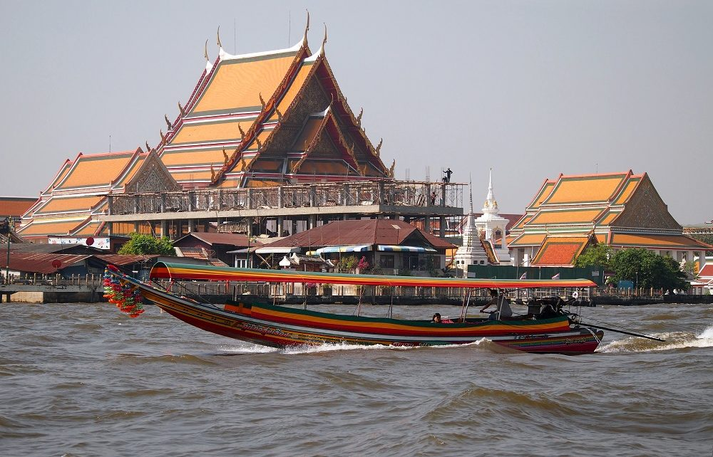 Longtail boat passing temples in Bangkok, Thailand