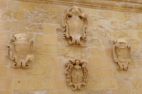 Stones crests on the walls of the citadel in Victoria, Gozo