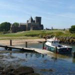 Boat at jetty with view of abbey on Inchcolm Island, Scotland