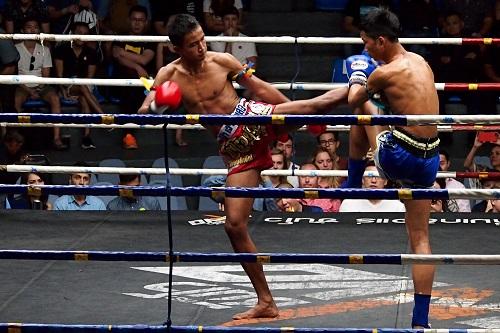 Muay Thai fighter blocks a kick at Rajadamnern Stadium in Bangkok, Thailand