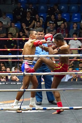 Referee overseeing Muay Thai fight at Rajadamnern Stadium in Bangkok, Thailand