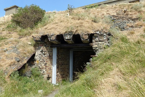 Entrance to WWI tunnel in grassy hillside at Inchcolm Island, Scotland